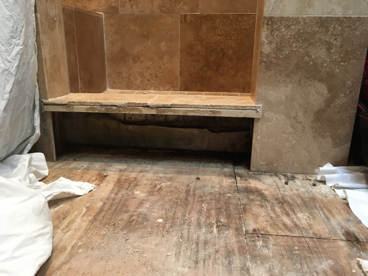 Looking through the demolished shower curb at the fiberglass waterproofing pan under the shower floor surface tile